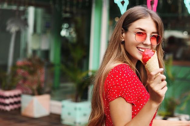 アイスクリームを食べて、カメラに微笑んで、夏休みを楽しんで、熱帯の島々への旅行をロマンチックな女性