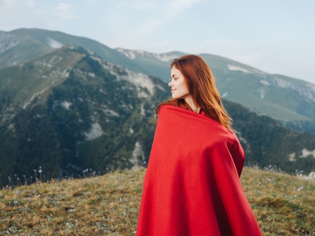 自然の中で屋外の山に赤い格子縞の後ろに隠れているロマンチックな女性