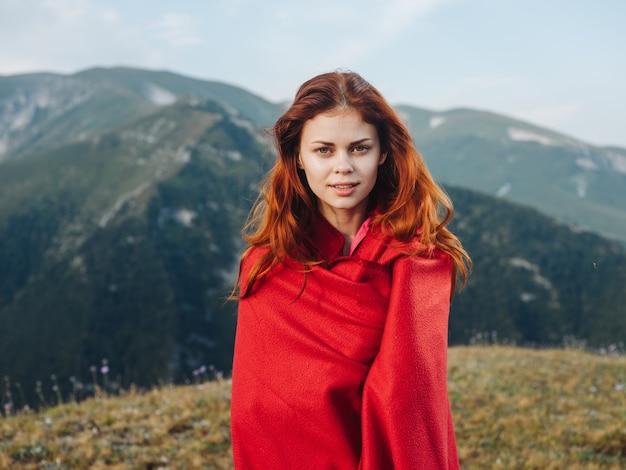 자연에서 야외 산에 붉은 격자 무늬 뒤에 숨어있는 로맨틱 여자.