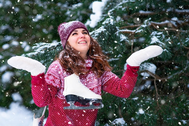 彼女の肩に冬のスケート靴を保持しているロマンチックな女性。冬の楽しみとスポーツ。女の子は冬の森で雪片をキャッチ