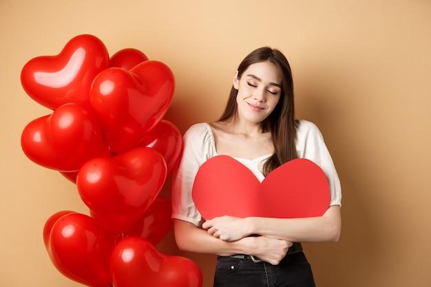 Романтичная женщина обнимает большое красное сердце и мечтательно улыбается, влюбляется в день святого валентина, мечтает о любовнике, стоя на бежевом фоне возле воздушных шаров.