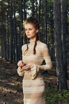Романтичная женщина в платье на свежем воздухе деревьев модели прически природы.