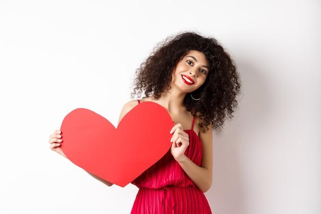 사랑에 빠지는 큰 붉은 마음을 보여주는 드레스 로맨틱 여자 카메라, 흰색 배경에 행복 미소.