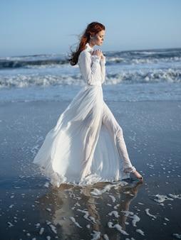 海の青い空のビーチで完全な長さのサンドレスのロマンチックな女性