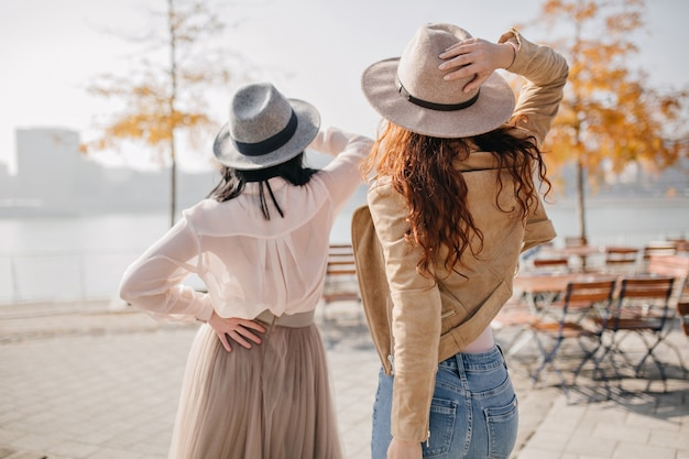 リボンで飾られた灰色の帽子のロマンチックな女性は暖かい秋の日にエレガントなスカートを着ています