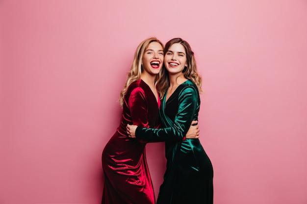 彼女の妹を抱きしめる緑のドレスを着たロマンチックな女性。笑っているベルベットの衣装で幸せな白人の女の子