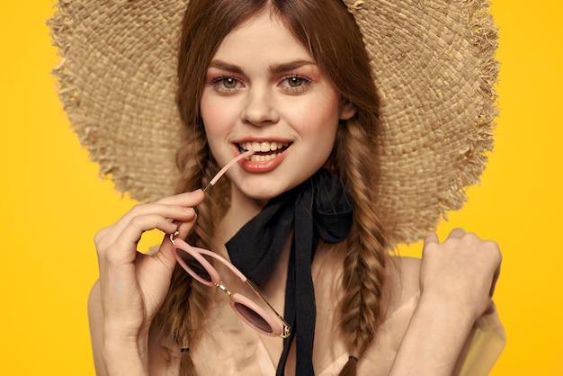 黄色の背景とサングラスの黒いリボンモデルで楽しんで帽子のロマンチックな女性