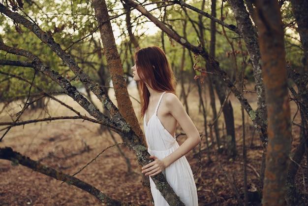 森の木々の近くの自然の中でロマンチックな女性。