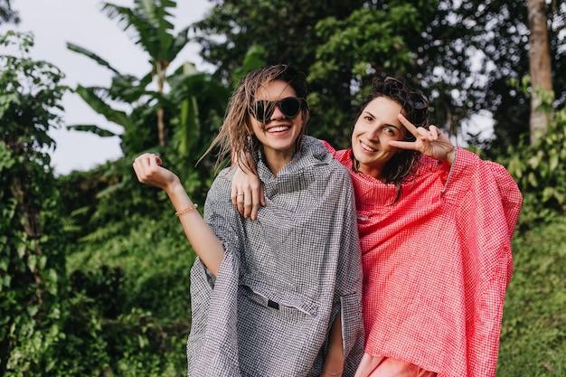친구 근처에 서있는 동안 평화 기호 포즈 핑크 비옷에 로맨틱 여자. 숲에서 쉬고 영감을 된 여성의 야외 촬영.
