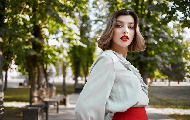 緑の木々の近くで夏に公園を歩くシャツのスカートのロマンチックな女性