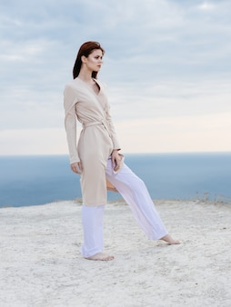 A romantic woman in light clothes walks on the sand and the ocean in the background