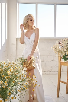 Romantic woman in a long white wedding dress is standing near the window in chamomile flowers