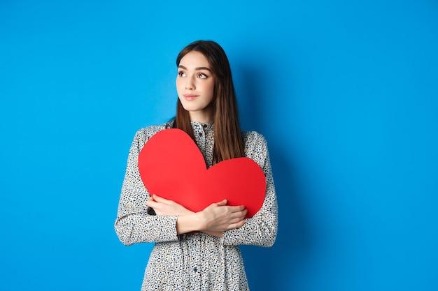 Романтичная женщина смотрит мечтательно, держа большое красное сердце
