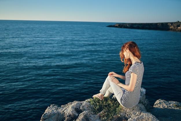 山の夕日の海の近くの岩の上のロマンチックな女性