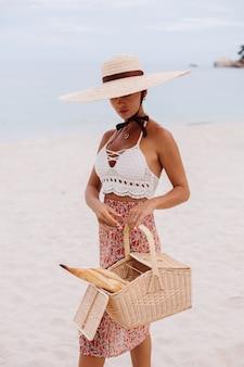 スカートニットトップとパンとバスケットを保持している麦わら帽子のビーチでロマンチックな女性エコライフ