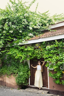 Romantic woman standing near old doors under a bush of blossoming bougainvillea