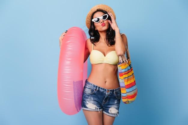 Donna romantica in occhiali da sole che tengono cerchio di nuoto