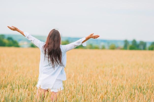 小麦の黄金のフィールドを歩いてロマンチックな女性