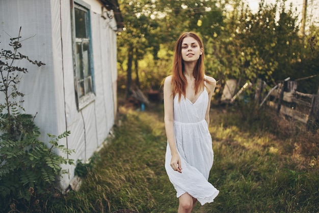 Romantic woman in white dress in countryside