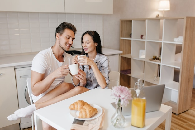 Romantic woman in white socks chilling with husband during breakfast and enjoying croissants