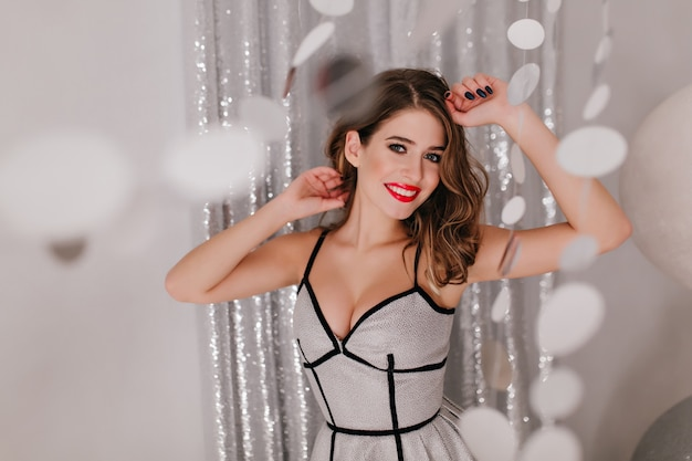 Romantic woman with black manicure posing before christmas party in decorated room.  shy girl with brown hair wears elegant sparkle dress.
