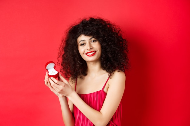 Romantic woman with curly hair, wearing red dress and showing engagement ring, standing happy on studio background.
