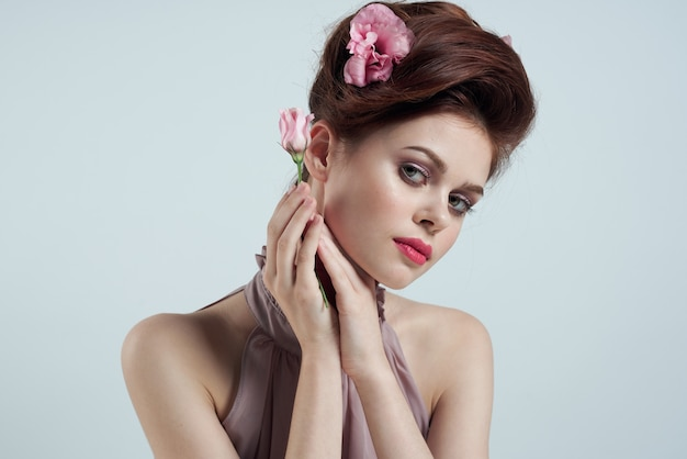 彼女の髪に花とピンクの花の光空間テーブルと花瓶でロマンチックな女性。