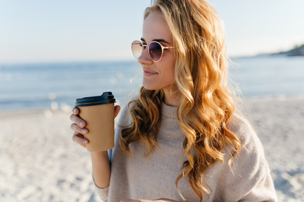 Donna romantica con capelli ling blinde bere il tè in mare. outdoor ritratto di donna affascinante in occhiali da sole guardando l'oceano nella mattina di autunno.