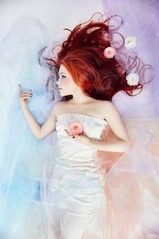 긴 머리와 구름 드레스를 입은 로맨틱한 여성. 밝은 화장과 완벽한 몸매를 꿈꾸는 소녀. 밝은 바람이 잘 통하는 색 드레스를 입은 빨간 머리 소녀는 바닥 흰색 배경에 놓여 있습니다. 소녀 머리에 아름다운 꽃