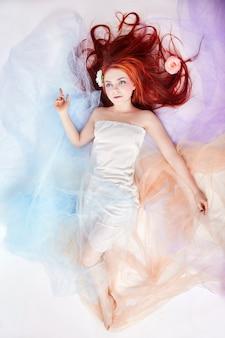 Романтичная женщина с длинными волосами и облачным платьем. девушка мечтает о ярком макияже и идеальном теле. рыжая девушка в легком воздушном цветном платье лежит на белом фоне пола. красивые цветы в волосах девушки
