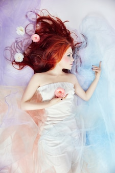 Romantic woman with long hair and cloud dress. woman dreaming bright makeup and perfect body. redhead woman in light airy colored dress lies