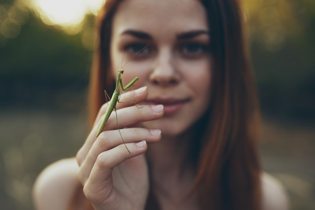 야외 초원에서 그녀의 손에 사마귀와 낭만적 인 여자.