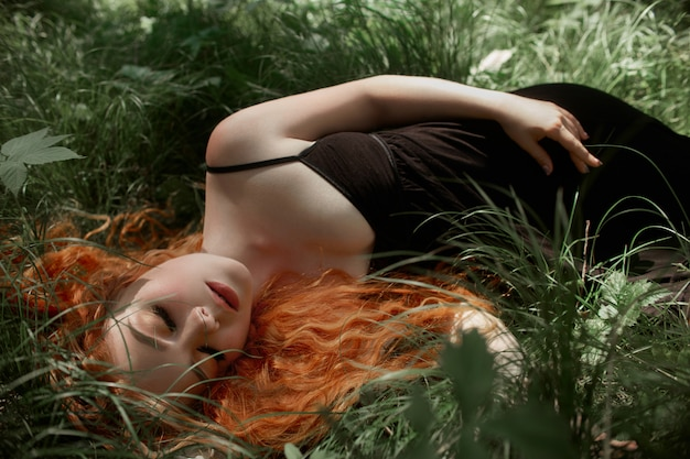 Romantic woman with red hair lying in the grass