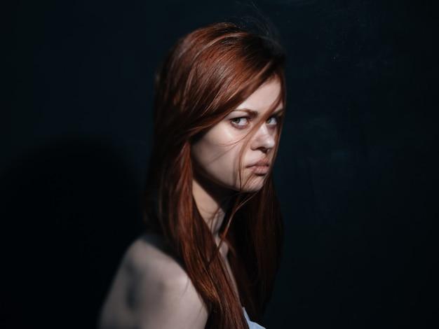 暗い背景モデルのクローズアップの肖像画に赤い髪のロマンチックな女性