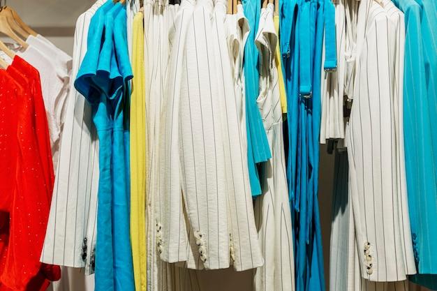 상점의 옷걸이에 있는 낭만적인 여성용 여름 드레스. 전면보기. 확대.