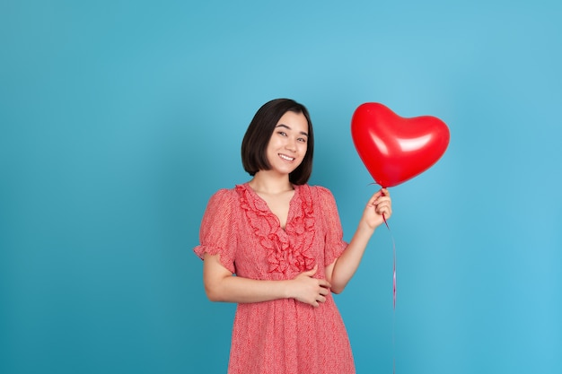 Romantic young asian woman in red dress and dark hair holding a flying red heart shaped balloon
