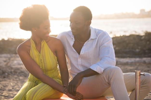 ロマンチックな若い黒人カップルの男性と女性は笑顔で、ビーチと夕日を背景に、日光と屋外の幸せな観光ライフスタイルの人々と一緒に余暇を過ごすのを楽しんでいます