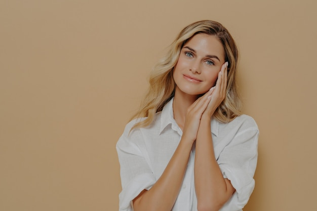 Романтичная молодая блондинка в повседневной белой рубашке держит сложенные руки возле лица и смотрит в камеру с нежной улыбкой, позирует на бежевом фоне с копией пространства. выражения человеческого лица