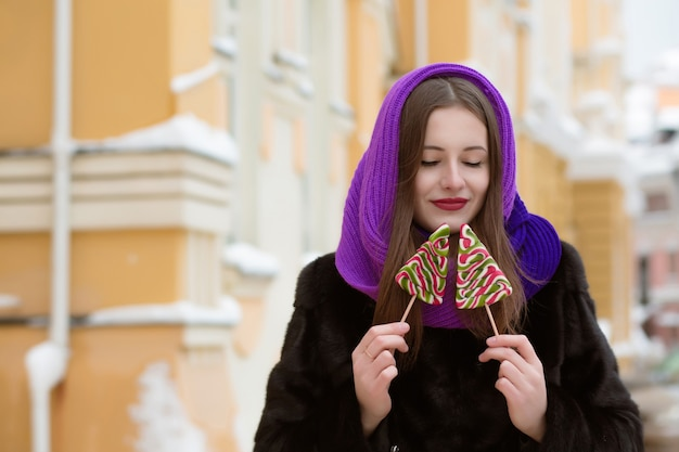 Romantic young  brunette woman in purple scarf holding colorful christmas candies