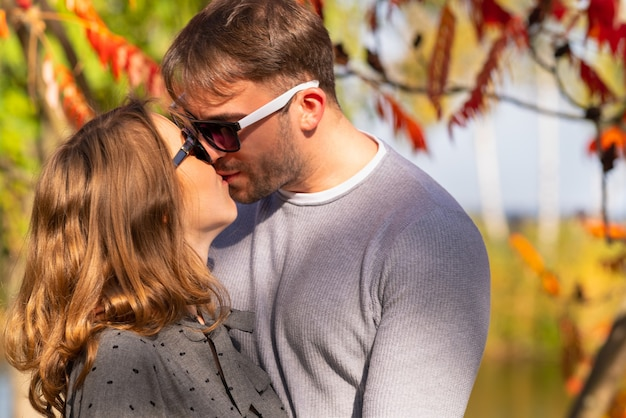 Romantic young coupe kissing in the garden in autumn against a colourful background of fall leaves