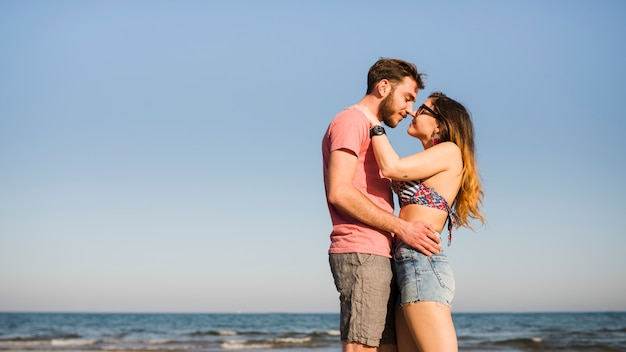 Romantic young couple against blue sky at beach