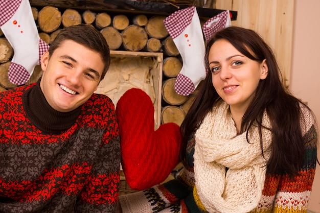 伝統的なクリスマスのストッキングと大きな赤いハートで飾られた素朴な木製の小屋でクリスマスを祝うロマンチックな若いカップル Premium写真