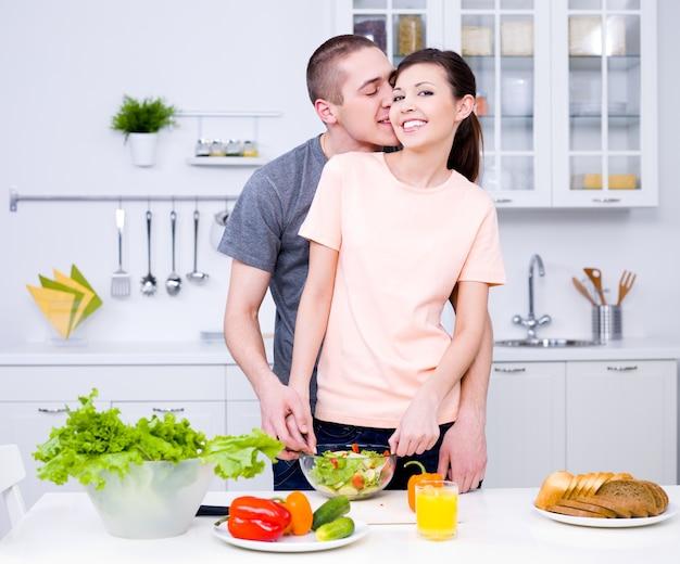 ロマンチックな若いカップルがキッチンで一緒に料理
