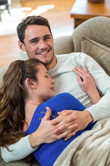 Romantic young couple cuddling on sofa in living room