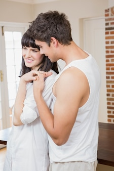Romantic young couple cuddling with each other in kitchen
