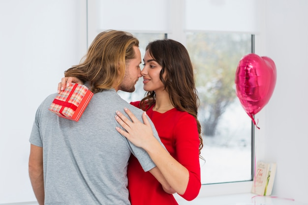 Romantic young couple embracing each other in front of window