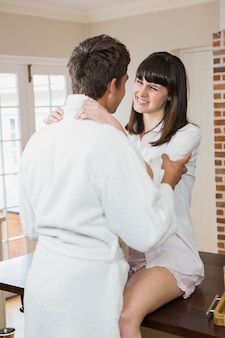 Romantic young couple embracing each other in kitchen