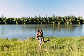 Romantic young couple enjoying near the beautiful calm lake