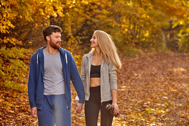 Romantic young couple enjoying walk in the autumn sunny forest, contemplating the nature, yellow trees around. hiking, autumn forest, walking, love concept