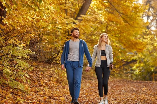 自然、周りの黄色い木々を熟考しながら、秋の日当たりの良い森の中を散歩を楽しんでいるロマンチックな若いカップル。ハイキング、秋の森、ウォーキング、愛の概念